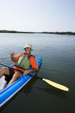 bald head island: African American middle-aged man smiling and giving thumbs up gesure in kayak.