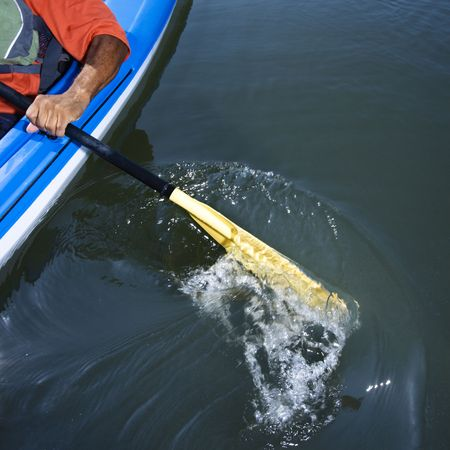 boater: African American male arm paddling kayak.
