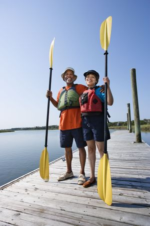 boater: African American middle-aged couple standing on boat dock holding paddles and smiling at viewer.