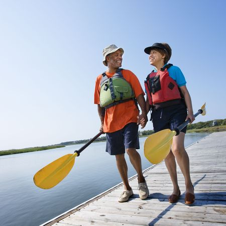 bald head island: African American middle-aged couple walking on boat dock holding hands and carrying paddles.