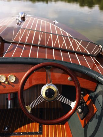 motorboat: Wooden boat with steering wheel and dashboard floating in gentle water.