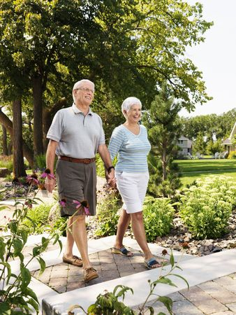Senior Caucasian couple holding hands and walking outdoors in park. photo