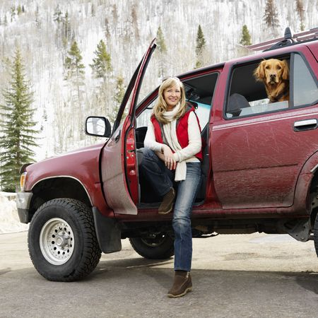 Woman sitting in dirt splattered SUV with door open as dog in back seat looks out open window in snowy countryside.