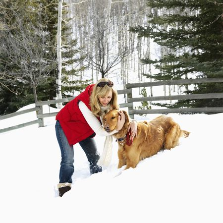 winter woman: Woman with arms around dog in snow covered Colorado landscape.