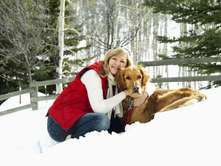 colorado landscape: Woman hugging dog and smiling in snow covered Colorado landscape.