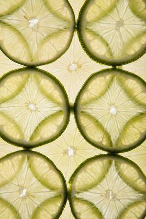 arranged: Lime slices arranged in  design on white background.