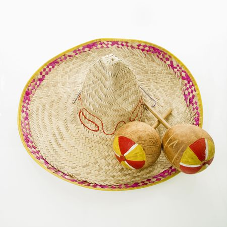 Pair of handmade Mexican maracas percussion musical instruments on sombrero straw hat.