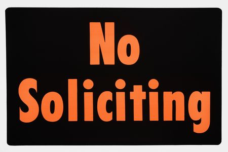soliciting: No soliciting sign with orange text against black. Stock Photo