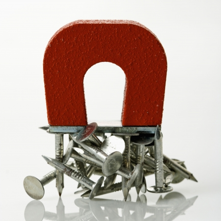 magnetism: Red magnet holding metal nails on white background. Stock Photo