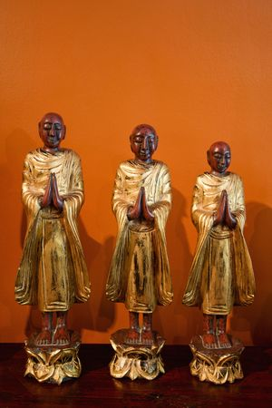 disciples: Three wooden statues of Buddhist disciples against orange wall.