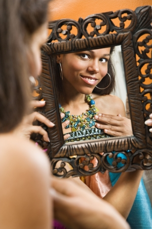 with reflection: African American mid adult woman smiling at reflection in mirror wearing necklace. Stock Photo