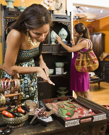 African American and Indian women shopping in boutique. photo