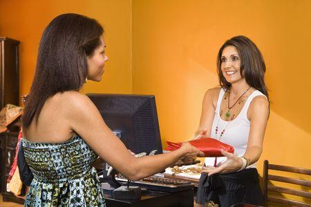 sales clerk: African American women handing item to sales clerk in boutique.