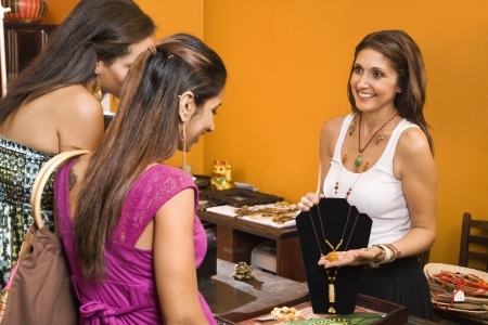 Sales clerk showing necklace to women shoppers in boutique. photo