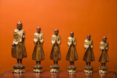 disciples: Wooden statues of Buddha with five disciples against orange wall.