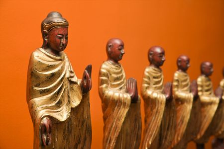disciples: Wooden statues of Buddha with disciples against orange wall.
