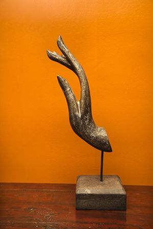 home accents: Carved hand sculpture from Thailand against orange wall.