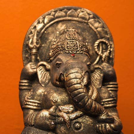 shree: Statue of Hindu elephant Ganesha against orange wall. Stock Photo