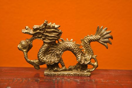 Chinese Taoist wisdom brass dragon statue against orange wall. photo