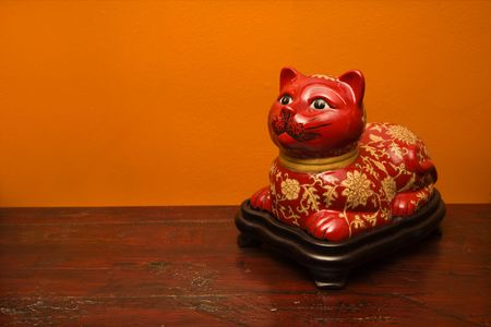 home accents: Chinese red cat statue against orange wall. Stock Photo
