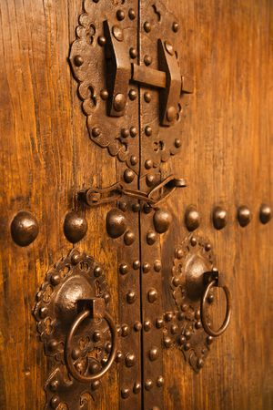 locked: Wooden doors with ornate metal knobs and locks.