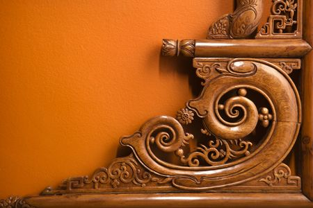 scroll: Ornate wooden Asian furniture carving against orange wall.