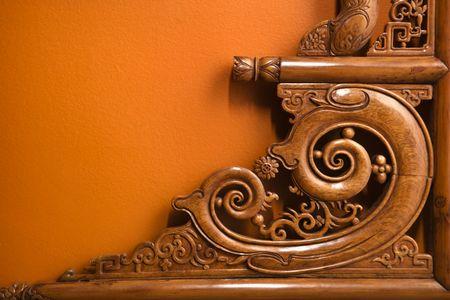 carve: Ornate wooden Asian furniture carving against orange wall.