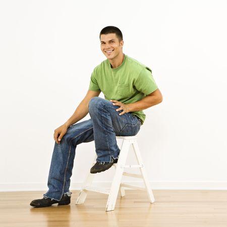 stepladder: Attractive man sitting on stepladder in home smiling.