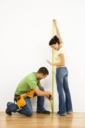 Couple measuring interior wall and smiling. photo