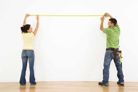 Couple measuring interior wall and smiling. Stock Photo - 2060979