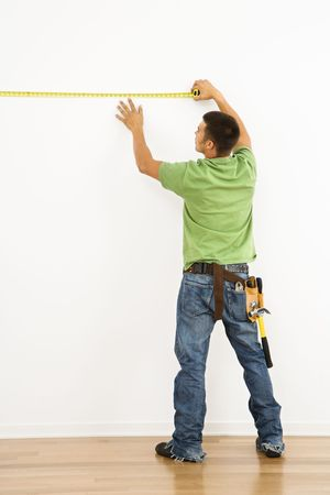 domestic scenes: Man wearing tool belt measuring interior wall. Stock Photo