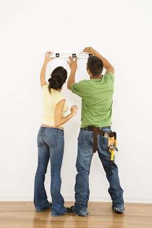 Couple holding level to interior wall and marking with pencil. Stock Photo