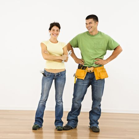 Couple with tools standing and smiling in home. photo