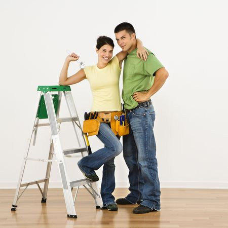 Couple with tools and ladder standing in home smiling. photo