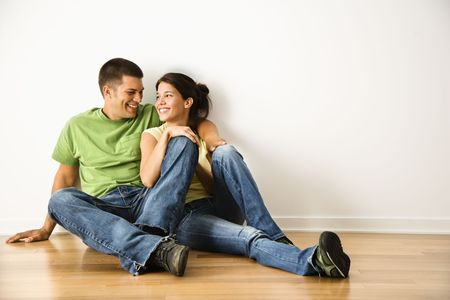 hardwood: Attractive young adult couple sitting close on hardwood floor in home smiling.