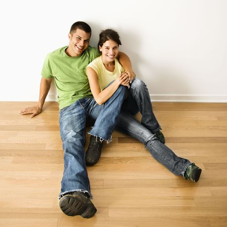 Attractive young adult couple sitting close on hardwood floor in home smiling. photo