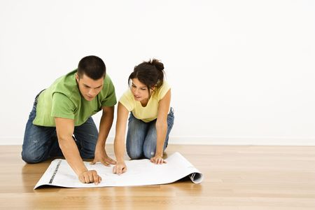 Attractive young adult couple looking at house plans. photo