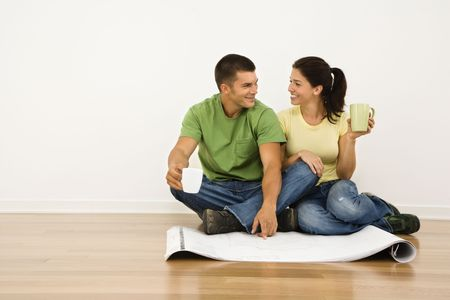 Attractive couple sitting on home floor with coffee cups looking at house plans and smiling at eachother. photo