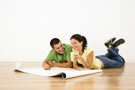 Attractive young adult couple lying on home floor with coffee cups smiling and looking at blueprints. photo