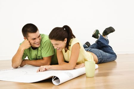 Attractive young adult couple lying on home floor with coffee cups smiling and looking at blueprints. Stock Photo - 2060907