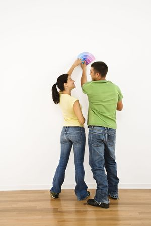 Attractive young adult couple holding color paint samples up to white wall. Stock Photo - 2060947