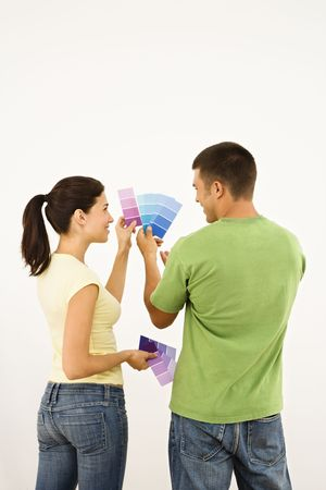 Attractive young adult couple holding color paint samples up to white wall. photo