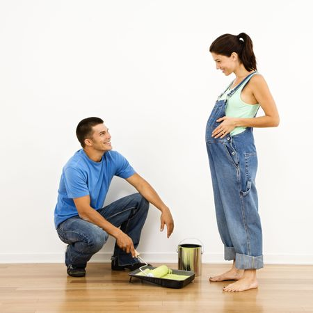 Pregnant woman and husband preparing to paint interior home wall. photo