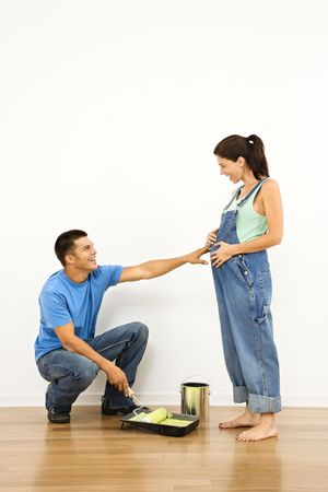 Pregnant woman and husband preparing to paint interior home wall. Stock Photo - 2060914