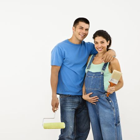Couple expecting  holding paintbrushes and smiling. Stock Photo - 2060916