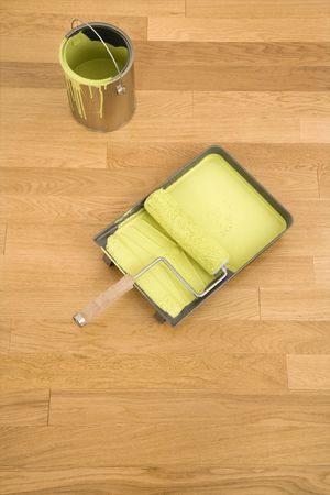Still life of paint roller in tray with paint can on wood floor. Stock Photo - 2043466