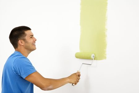 man painting: Attractive smiling man painting white wall with green paint.