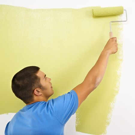 man painting: Man painting over white wall with green paint using paint roller. Stock Photo
