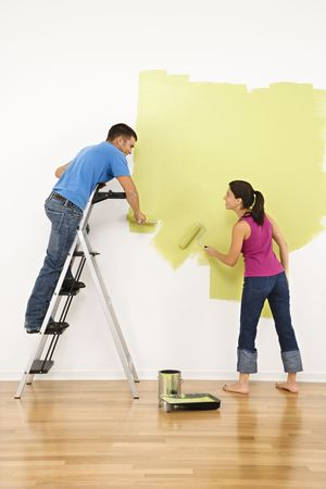 painting: Attractive young adult couple painting interior wall of house.