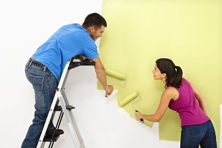 hombre pintando: Atractivo joven adulto joven pintura pared interior de la casa.  Foto de archivo